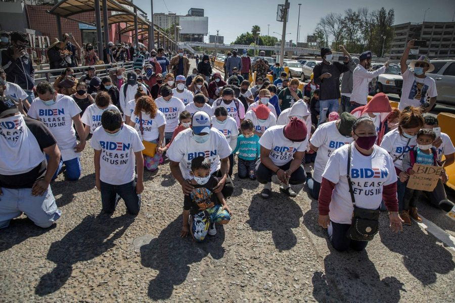 "A group of migrants wearing T-shirts that read, ""Biden, please let us in,"" kneel and pray at the border crossing on March 2, 2021 in San Ysidro, Mexico. The group gathered and marched up to the border post to petition the new U.S. administration for asylum. U.S. Border Patrol (CPB) agents conducted a heavier operation at the border crossing with the goal of preventing a stampede. (Stringer/dpa via ZUMA Press/TNS)"
